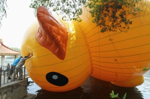 Employees try to push a scaled replica of the rubber duck by Dutch conceptual artist Florentijn Hofman away from lakeside at a park in Shenyang